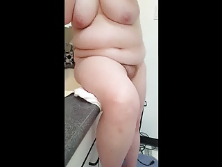 sitting by the mirror fixing her face, hair, big tits